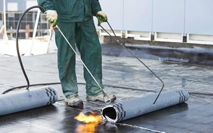Het vastbranden van bitumen dakbedekking aan de dakisolatie dat op de onderconstructie zit. Dakdekker plat dak